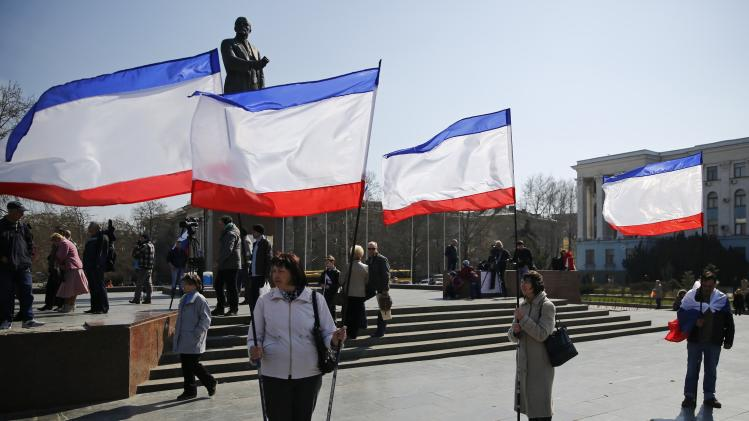 People hold Crimean flags during a pro-Russian rally on the eve of a referendum in Lenin Square in Simferopol