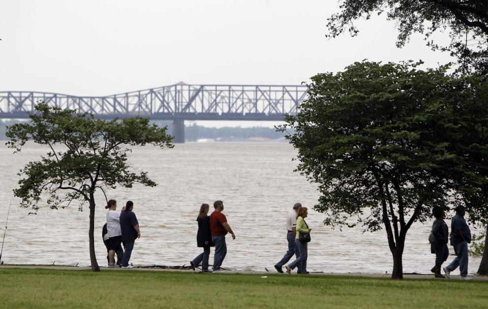 Pedestrians walk along a riverside park as floodwaters are seen in the background Saturday, May 7, 2011, in Memphis, Tenn. Communities all along the banks of the Mississippi are keeping a close eye on the river's rise with the crest in Memphis not expected until Wednesday. (AP Photo/Jeff Roberson)