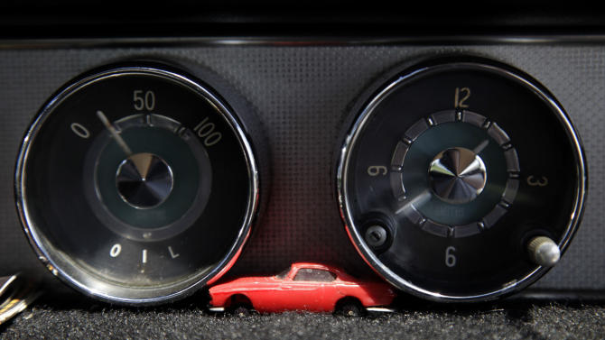 A miniature car rests on the dashboard of Irv Gordon's Volvo P1800 in Babylon, N.Y., Monday, July 2, 2012. Gordon's car already holds the world record for the highest recorded milage on a car and he is less than 40,000 miles away from passing three million miles on the Volvo.  (AP Photo/Seth Wenig)