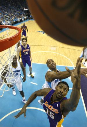 Los Angeles Lakers forward Ron Artest (15) shoots past New Orleans Hornets guard Jarrett Jack, center, and center Emeka Okafor during the first half of Game 6 of a first-round NBA basketball playoff series in New Orleans, Thursday, April 28, 2011. (AP Photo/Patrick Semansky)