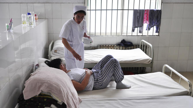 In this May 11, 2012 photo, a nurse brings food to a patient who refused to leave her bed at a psychiatric hospital in Zouping county, in eastern China's Shandong province. China's legislature on Friday, Oct. 26, 2012, passed a long-awaited mental health law that aims to prevent people from being involuntarily held and treated in psychiatric facilities - abuses that have been used against government critics and have triggered public outrage. (AP Photo) CHINA OUT