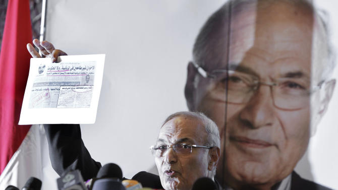 """Egyptian presidential candidate Ahmed Shafiq holds a clipping from an Arabic newspaper with a headline that reads, """"The Muslim Brotherhood--not suited for presidency or government,"""" during a press conference in Cairo, Egypt, Sunday, June 3, 2012. Shafiq, the last prime minister of deposed President Hosni Mubarak, will face the Muslim Brotherhood candidate Mohammed Morsi in a run-off on June 16-17. (AP Photo/Amr Nabil)"""