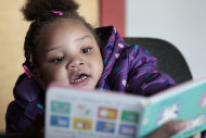 In this photo taken Dec. 8, 2011, Taliyah Garrett, 3, looks at a book as she gets help in learning to read by a coordinator from the Parent Child Home Program during a visit in Seattle. The home visiting program, supported by United Way of King County, Wash., helps children from low-income families prepare for kindergarten by tutoring parents in how to teach their children. As the first signs of an economic recovery make the news, many of the nation's nonprofit organizations are digging in for another three to four years of financial distress, according to researchers who keep an eye on the chartable world. (AP Photo/Elaine Thompson)