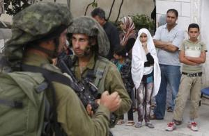 Palestinians stand outside their house as Israeli soldiers take part in an operation to locate three Israeli teens near the West Bank City of Hebron