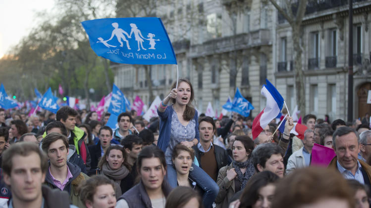 "Anti gay marriage activists wavs a flag with the logo of the movement on it during a rally to protest against the new law after French lawmakers legalized same-sex marriage, Tuesday, April 23, 2013 in Paris. Lawmakers legalized same-sex marriage after months of bruising debate and street protests that brought hundreds of thousands to Paris. Tuesday's 331-225 vote came in the Socialist majority National Assembly. France's justice minister, Christiane Taubira, said the first weddings could be as soon as June. Flags read, ""demonstration for all."" (AP Photo/Michel Euler)"