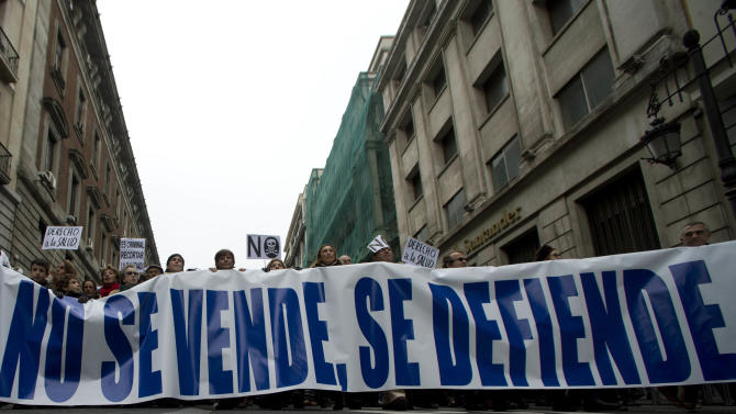 National health workers march during the first major demonstration of the year, in Madrid Monday Jan. 7, 2013. The demonstration was against government-imposed austerity measures and labor reforms in the public health care sector in Madrid. Main banner reads' Don't sell it, defend it' (AP Photo/Paul White)