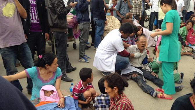 An injured man receives treatment outside the Medicare Hospital in Kathmandu, Nepal, Saturday, April 25, 2015. A strong magnitude-7.9 earthquake shook Nepal's capital and the densely populated Kathmandu Valley before noon Saturday, causing extensive damage with toppled walls and collapsed buildings, officials said. (AP Photo/ Niranjan Shrestha)