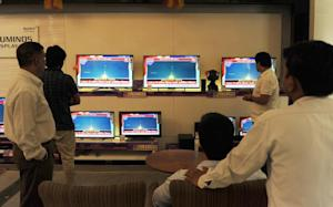 Indian bystanders watch a bank of screens showing the …