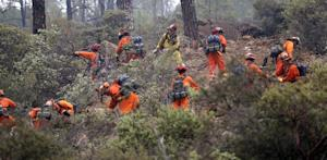 Firefighters work on a ridge line as they clear brush…