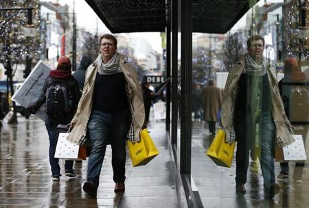 Christmas shoppers walk along Oxford Street in central London