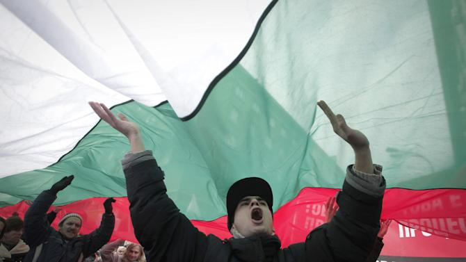 "Bulgarian shouts slogans as they carry giant Bulgarian flag  during a protest against higher electricity and heating bills, in Sofia,  Sunday, Feb. 17, 2013. Thousands of angry Bulgarians chanted ""mafia"" and ""resignation""  demanded the expulsion of the three foreign-controlled power distributors that control the local market: Czech Republic's CEZ and Energo-Pro, and Austria's EVN   (AP Photo/Valentina Petrova)"