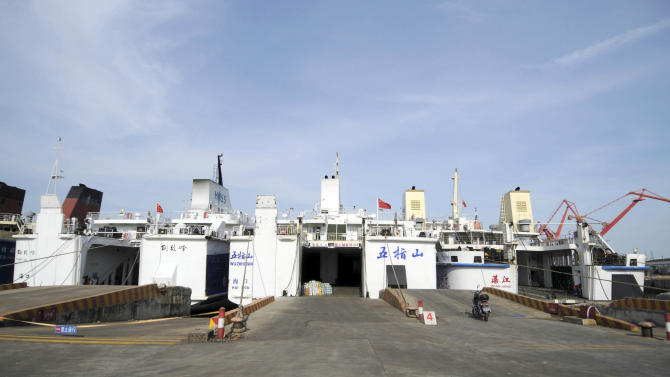 In this Sunday, May 18, 2014 photo released by China's Xinhua News Agency, passenger ships Wuzhishan, center, and Tongguling, left, are moored before setting sail to Vietnam , at Xiuying port in Haikou, capital of south China's Hainan Province. A port official said the two Chinese passenger ships have arrived at a central Vietnamese port to evacuate Chinese nationals following deadly rioting last week. The official said the boats with a capacity of 1,000 passengers each arrived at Vung Ang early Monday, May 19. (AP Photo/Xinhua, Wei Hua) NO SALES