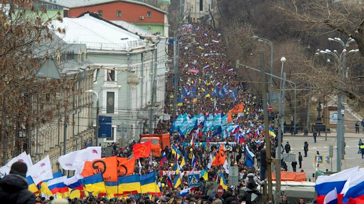 Protesters carry Ukrainian and Russian flags in Moscow, on March 15, 2014, during a rally against Russia's recent intervention in Crimea