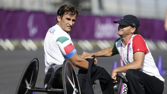Alessandro Zanardi, left, of Italy looks back down the track as he watches other competitors finish after he competed in the man's road cycle individual time trial H4 category at the 2012 Paralympics games, Wednesday, Sept. 5, 2012, in London. (AP Photo/Alastair Grant)