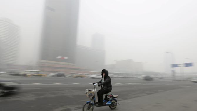 A woman wearing a mask cycles amid heavy smog in Beijing's Guomao area
