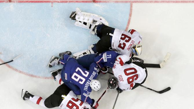 France's Dieude-Fauvel and Guttig challenge Switzerland's Wieser, Josi and goaltender Genoni during their Ice Hockey World Championship game at the O2 arena in Prague