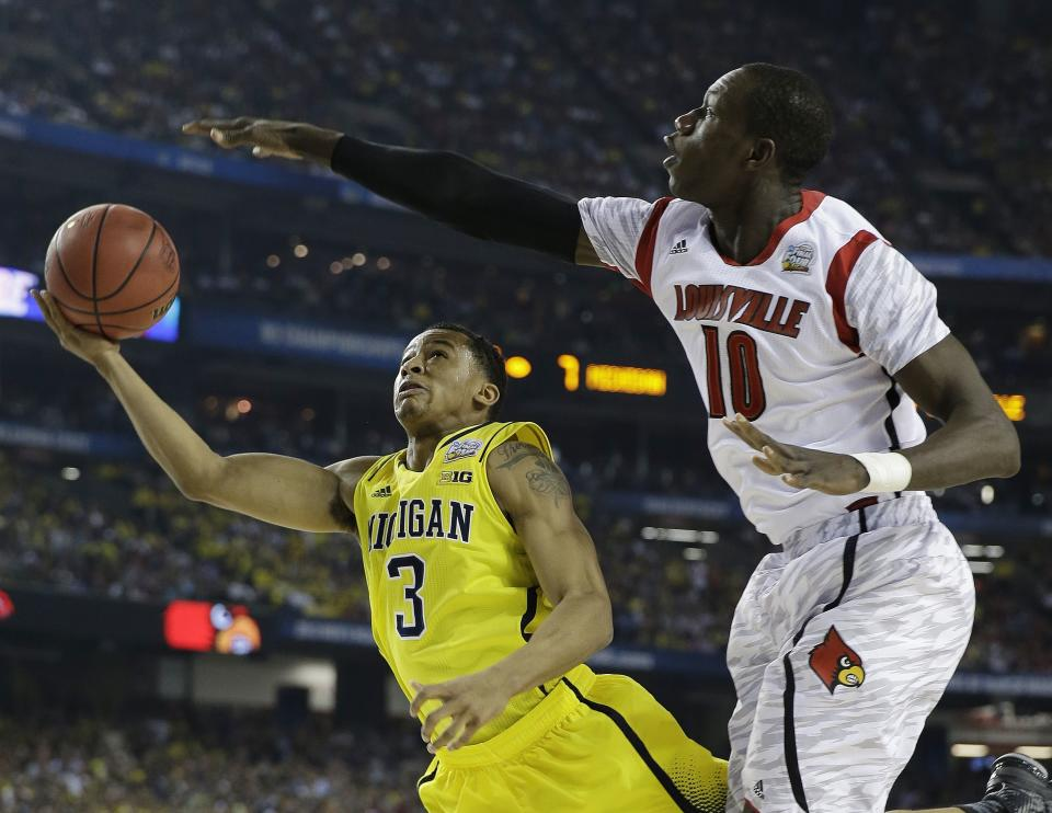 Michigan guard Trey Burke (3) shoots against Louisville center Gorgui Dieng (10) during the first half of the NCAA Final Four tournament college basketball championship game Monday, April 8, 2013, in Atlanta. (AP Photo/David J. Phillip)