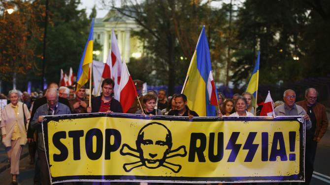 People hold a banner with the words 'Stop Russia'  in front of Russian embassy in Warsaw