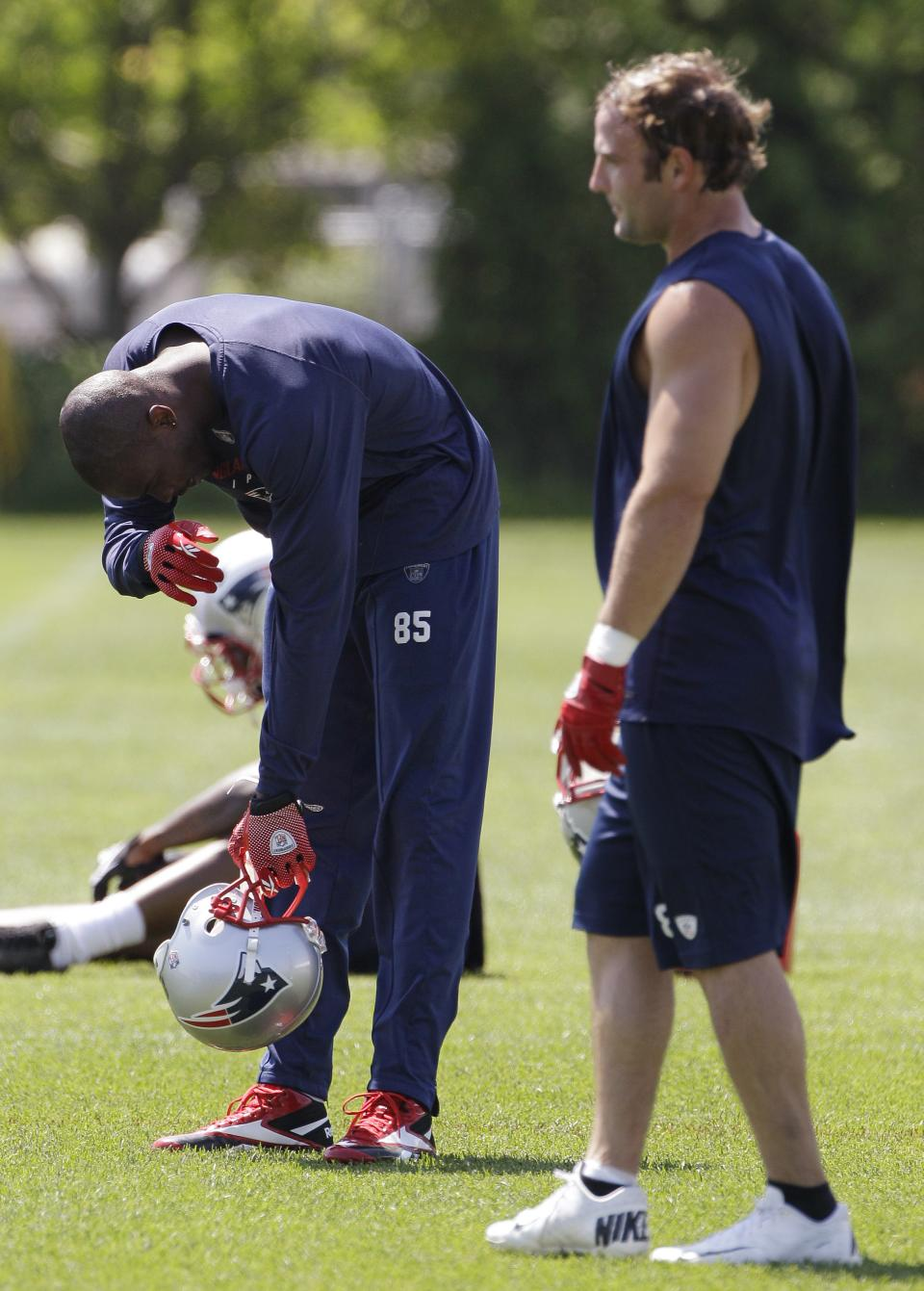 New England Patriots wide receiver Chad Ochocinco, left, wipes his brow as wide receiver Wes Welker walks by during NFL football practice at the team's training facility in Foxborough, Mass., Thursday, May 31, 2012. (AP Photo/Stephan Savoia)