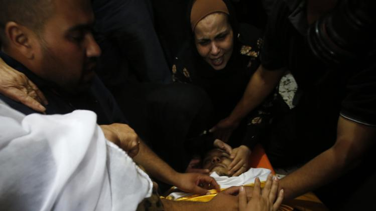 Relatives of Palestinian Eid Rabah Fdilat, whom medics said was killed during clashes with Israeli troops on Friday, mourn around his body during his funeral in Arroub refugee camp, north of the West Bank city of Hebron