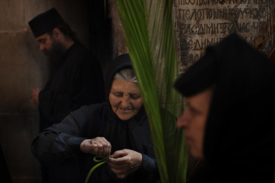 A Greek Orthodox nun makes a palm ribbon before attending a vesper ceremony inside the Church of the Holy Sepulchre, traditionally believed to be the burial site of Jesus Christ, in Jerusalem's Old City, Saturday, April 7, 2012. (AP Photo/Bernat Armangue)