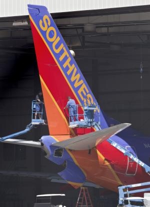 Workers inspect a tail fin of a Southwest jet Monday, April 4, 2011 at Southwest's maintenance facility at Sky Harbor International Airport in Phoenix. The peeling away of a 5-foot-long hole recently on a Southwest Jet as the plane traveled at 35,000 feet raised questions about how vulnerable the world's passenger air fleet is to similar cracks, and federal aviation officials were considering ordering more widespread inspections. (AP Photo/Matt York)