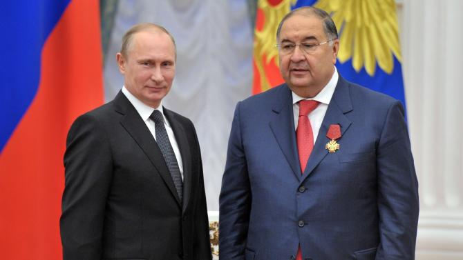 FILE - In this Tuesday Oct. 29, 2013 file photo Russian President Vladimir Putin presents a medal to Russian billionaire tycoon Alisher Usmanov, right, at the award ceremony in the Kremlin in Moscow, Russia. A media company owned by Kremlin-friendly oligarch Alisher Usmanov has splashed out $1.5 billion to gain full control of Russia's most popular social network, VKontakte, bringing an end to a months-long dispute that saw the original investors sue each other in court. London-listed Mail.Ru Group said in a statement Tuesday Sept. 16, 2014 that it now owns the whole of VKontakte following its purchase of a 48 percent stake from investment fund United Capital Partners. (AP Photo/RIA Novosti, Alexei Nikolsky, Presidential Press Service, File)