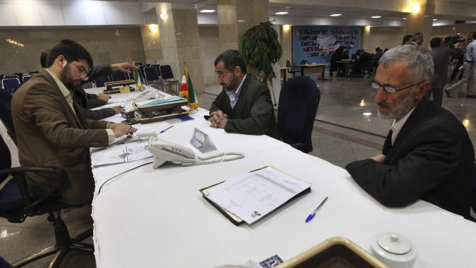 Two Iranians, right, visit the election headquarters of the interior ministry to register their candidacy for upcoming presidential election, as an election worker submits the names, left, in Tehran, Iran, Tuesday, May 7, 2013. Iranian authorities opened the registration process Tuesday for candidates in next month's presidential election that will pick a successor to President Mahmoud Ahmadinejad and offer a critical test for reformists battered after years of crackdowns.(AP Photo/Vahid Salemi)