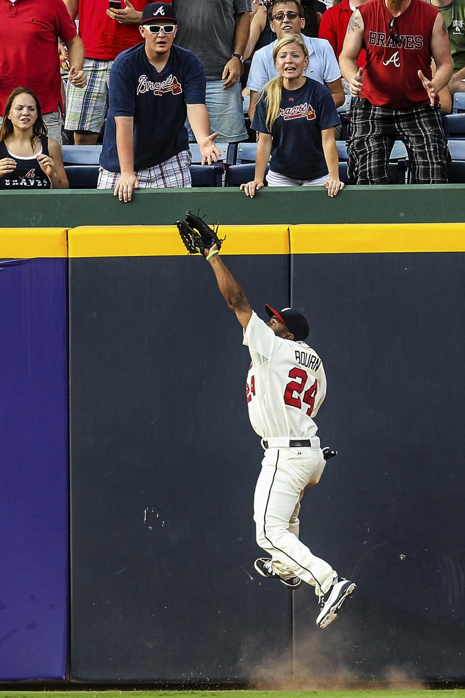 Atlanta Braves center fielder Michael Bourn (24) makes a leaping catch on a fly ball by Philadelphia Phillies' Chase Utley in the sixth inning of a baseball game, Sunday, Sept. 2, 2012, in Atlanta. (AP Photo/Daniel Shirey)