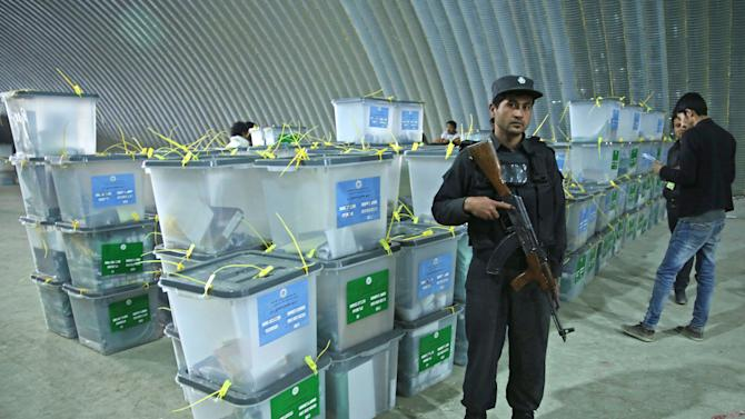 An Afghan police officer stands guard as Afghan election workers, right, note serial numbers of ballot boxes at a warehouse of the Independent Elections Commission warehouse in Kabul, Afghanistan, Sunday, April 6, 2014. Trucks and donkeys loaded with ballot boxes made their way to counting centers on Sunday as Afghans and the international community sighed with relief that national elections were held without major violence despite a Taliban threat. (AP Photo/Massoud Hossaini)
