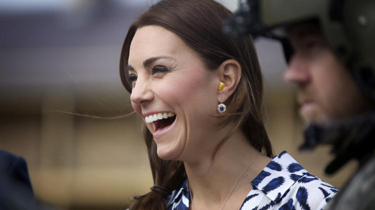 Catherine, Duchess of Cambridge, laughs as she puts on earplugs as they prepare to board a Royal Australian Navy MRH90 helicopter at Sydney's Victoria Barracks