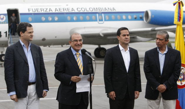 Humberto de la Calle, second from left, head of Colombia's peace negotiation team, speaks to journalists before embarking to Havana for a round of peace talks with rebels of the Revolutionary Armed Forces of Colombia, FARC, at the military airport in Bogota, Colombia, Sunday, Nov. 18, 2012. His is accompanied by government negotiators Sergio Jaramillo, right, former Gen. Jorge Mora, right, and Frank Pearl, second from right. (AP Photo/William Fernando Martinez)