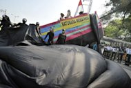 "Greenpeace activists wearing black suits stand beside a symbolic boat (top) with a banner that reads ""coal kills"" attend a rally outside the Maritime and Fisheries Ministry in Jakarta. Greenpeace activists Wednesday protested plans by Indonesia to build Southeast Asia's biggest coal power plant, saying it would sully coastal waters and strip the livelihoods of fishermen and farmers"