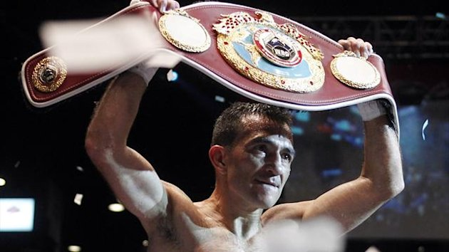 World Boxing Organization (WBO) champion Omar Narvaez of Argentina holds up his belt after defeating Felipe Orucuta of Mexico in their super flyweight world title bout at the Luna Park Arena in Buenos Aires May 26, 2013. REUTERS