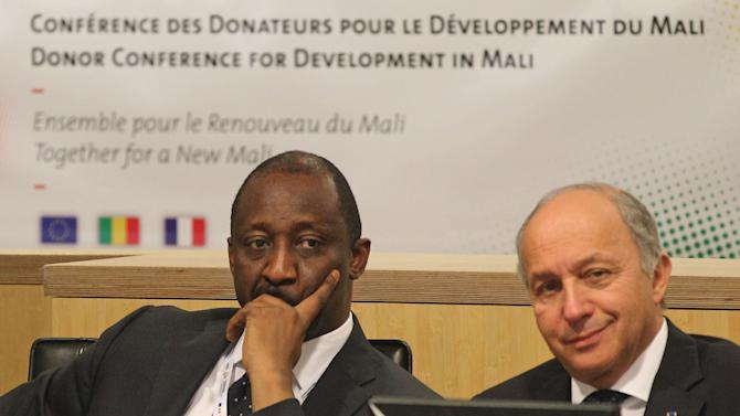 French Foreign Minister Laurent Fabius, right, and his Mali counterpart Tieman Coulibaly listen during the Donor Conference for Development in Mali, in Brussels, Wednesday, May 15, 2013. Mali aims to raise 2 billion euros ($2.6 billion) at an international donor conference to fund its recovery after Islamist militants marched on Bamako this year, prompting a French military intervention. (AP Photo/Yves Logghe)