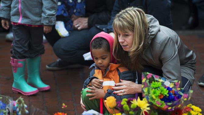 A woman and child participate in a candlelight vigil in Moncton, New Brunswick, on Friday, June 6, 2014, to pay respects to the three Royal Canadian Mounted Police officers who were killed and the two injured in shootings Wednesday. Suspect Justin Bourque, 24, was caught early Friday, ending a 30-hour manhunt that closed schools and forced residents to hide inside their homes. (AP Photo/The Canadian Press, Andrew Vaughan)