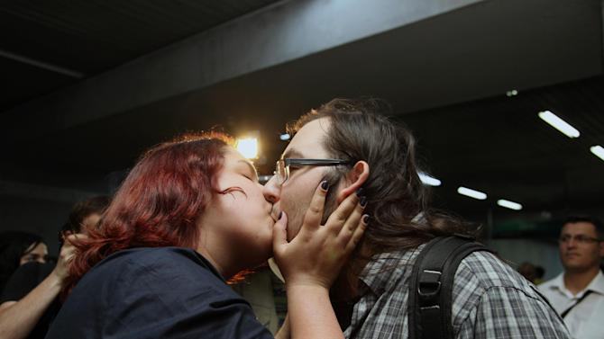 """A young Turkish couple kiss to protest against subway official's harassment of a couple for kissing in public last week, inside a subway stop in Ankara, Turkey, Saturday, May 25, 2013.  Last week, Ankara subway officials made a reproaching announcement asking passengers """"to act in accordance with moral rules,"""" after spotting the couple kissing through security cameras.(AP Photo/Burhan Ozbilici)"""