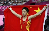 China's gymnast Zou Kai celebrates with his national flag after winning the men's floor exercise final of the artistic gymnastics event of the London Olympic Games at the 02 North Greenwich Arena in London. Zou won the gold medal