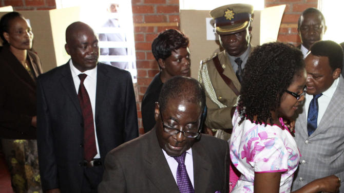 Zimbabwean President Robert Mugabe casts his vote for a referendum on a new constitution that all main political parties have backed in Harare, Saturday, March 16, 2013. Officials said polling was busy in populous districts after voting stations opened at 7.00 a.m. (0500 GMT) across the country. The proposed constitution reduces the entrenched powers of Zimbabwe's president and includes a range of democratic reforms demanded by regional mediators in Zimbabwe's decade-long political and economic crisis. (AP Photo/Tsvangirayi Mukwazhi)