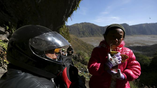 A Hindu father and his daughter drink holy water they collected from a stream for prayers ahead of the annual Kasada festival at Mount Bromo