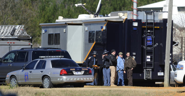 Law officers stand beside the Alabama State trooper mobile command post at the Dale County hostage scene in Midland City, Ala. on Thursday, Jan. 31, 2013. A gunman holed up in a bunker with a 6-year-o