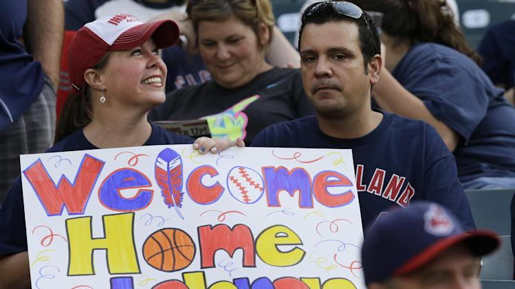 A fan holds a sign welcoming LeBron James back to Cleveland, before a baseball game between the Chicago White Sox and Cleveland Indians on Friday, July 11, 2014, in Cleveland. James announced earlier in the day he will return to play for the Cleveland Cavaliers. (AP Photo/Mark Duncan)