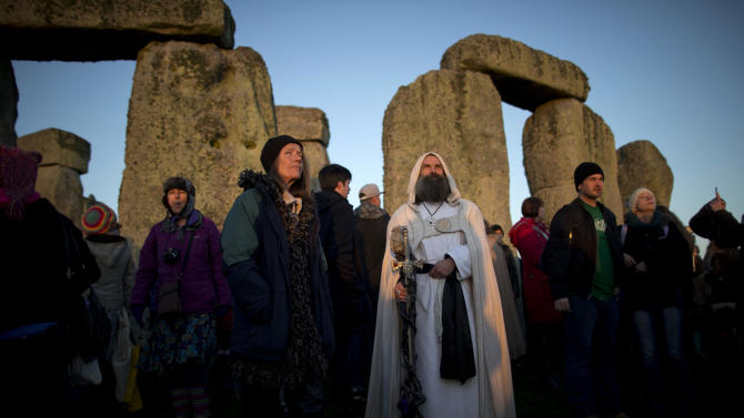 "A druid watches the sunrise by the ancient stone circle of Stonehenge, in southern England, as access to the site is given to druids, New Age followers and members of the public on the annual Winter Solstice, Friday, Dec. 21, 2012.  Doomsday hour is here and so still are we.  According to legend, the ancient Mayans' long-count calendar ends at midnight Thursday, ushering in the end of the world. Didn't happen.  ""This is not the end of the world. This is the beginning of the new world,"" Star Johnsen-Moser, an American seer, said at a gathering of hundreds of spiritualists at a convention center in the Yucatan city of Merida, an hour and a half from the Mayan ruins at Chichen Itza.  (AP Photo/Matt Dunham)"