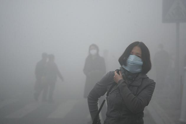 A woman wearing a mask walk through a street covered by dense smog in Harbin, northern China, Monday, Oct. 21, 2013. Visibility shrank to less than half a football field and small-particle pollution s