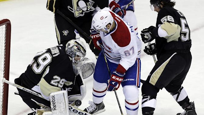 Montreal Canadiens left wing Max Pacioretty (67) looks for the rebound between Pittsburgh Penguins goalie Marc-Andre Fleury (29), and Pittsburgh Penguins defenseman Kris Letang (58) in the first period of an NHL hockey game in Pittsburgh Tuesday, March 26, 2013. (AP Photo/Gene J. Puskar)