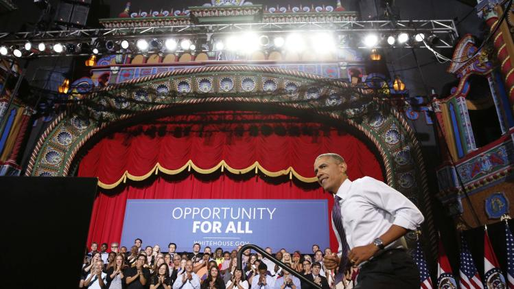 U.S. President Barack Obama walks in before he speaks about the economy at the Uptown Theater in Kansas City