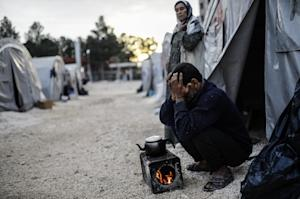 A Syrian Kurdish man brews tea in front of his tent…