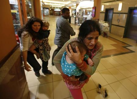 Women carrying children run for safety as armed police hunt gunmen who went on a shooting spree in Westgate shopping centre in Nairobi September 21, 2013. REUTERS/Goran Tomasevic