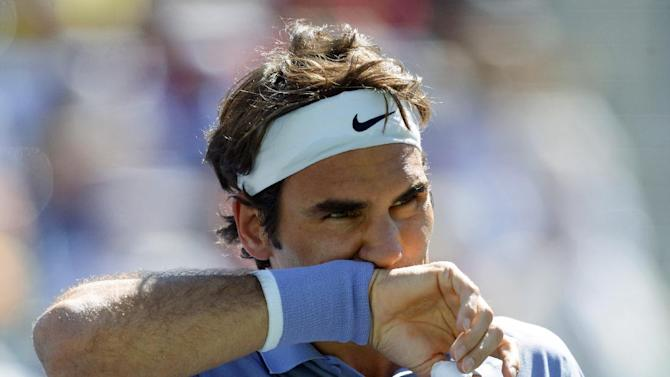 FILE - In this March 16, 2014 file photo, Roger Federer of Switzerland wipes his face during the BNP Paribas Open tennis tournament in Indian Wells, Calif. Federer announced on Tuesday May 6, 2014 that has withdrawn from the Madrid Open to spend more time with his family ahead of the birth of his third child. Federer's announcement means he will likely miss the Rome Masters next week. (AP Photo/Mark J. Terrill, File)