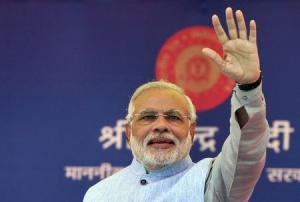 Indian PM Modi waves to a crowd at a gathering after inaugurating a train on a new stretch of railway to the town of Katra